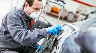 Ein Mitarbeiter trägt eine Atemmaske bein Entlacken eines Bauteils
